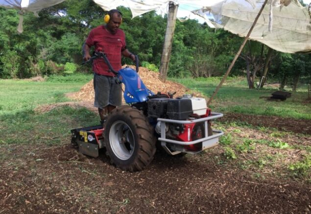 Using the two-wheeled tractor and power harrow to prepare beds for planting on the Naitauba farm.